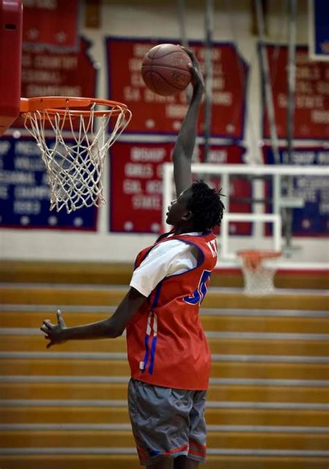 Bol Bol, 14 years old and 6 feet 10, reaches for his